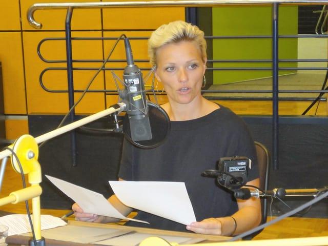 Susanne Kunz sitzt an einem Sprecherpult mit Manuskript.