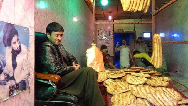 Eine Bäckerei mit Fladenbrot in Kabul. Im Vordergrund ein junger Mann, der Bäcker.