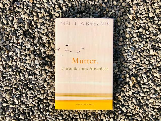 «Mutter. Chronik eines Abschieds» von Melitta Breznik liegt auf einem Kiesboden