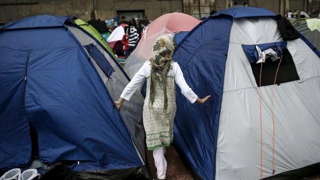 Ein Mädchen mit Kopftuch läuft an aufgestellen Zelten vorbei. Von hinten gesehen.