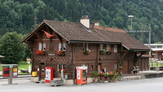 Bahnhof Trun, dunkel gebeizter Holzsbau mit Giebeldach und Geranien