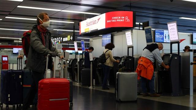 Passagiere mit Schutzmaske checken am Flughafen Wien ein.