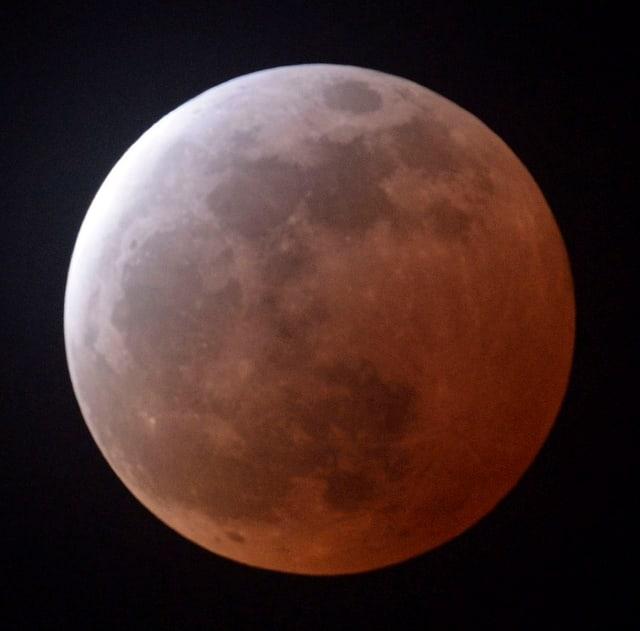 Im linken oberen Bereich ist der Mond weiss, in der unteren rechten Hälfte rötlich. Dazwischen schimmert der Mond gräulich.
