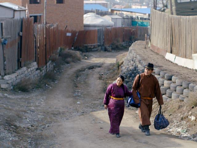 Zwei Personen in traditionellen mongolischen Kleidern gehen durch eine Stadt.