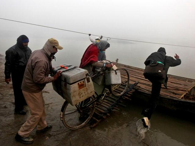 Männer schieben ein schwer beladenes Fahhrad auf ein Floss.