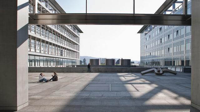 Blick auf einen Betonplatz, darauf sitzen zwei junge Frauen am Boden. Rundherum Gebäude mit Glasfassade.