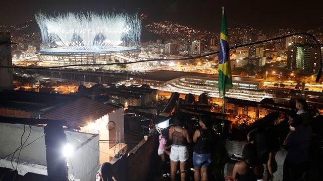 Bewohner der Mangueira-Favela schauen die Eröffnungsfeier aus der Ferne.