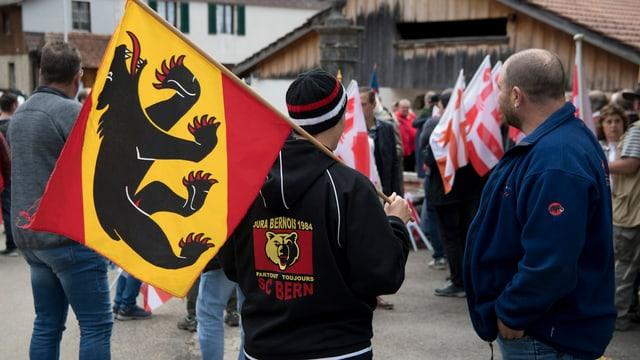 Votants e votantas cun bandieras dals chantuns Berna e Giura.
