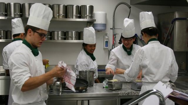 Fünf Studenten räumen die Küche auf.