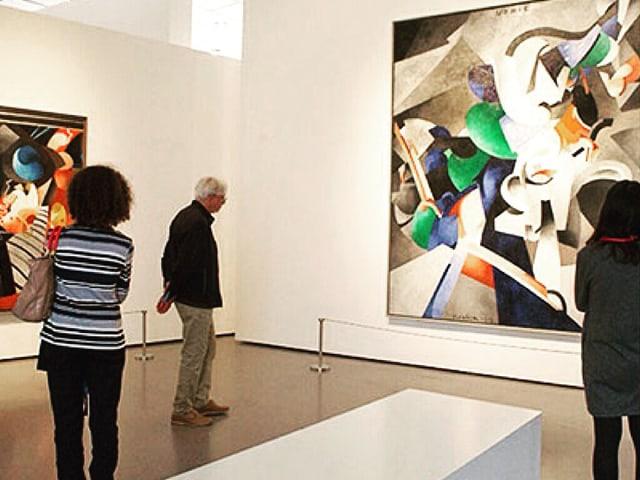 Ausstellungsraum mit Gemälden und Zuschauern.