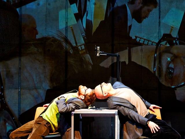 Zwei Männer lehnen auf Tisch auf Bühne