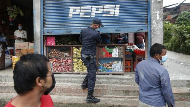 Polizist schliesst einen Laden.