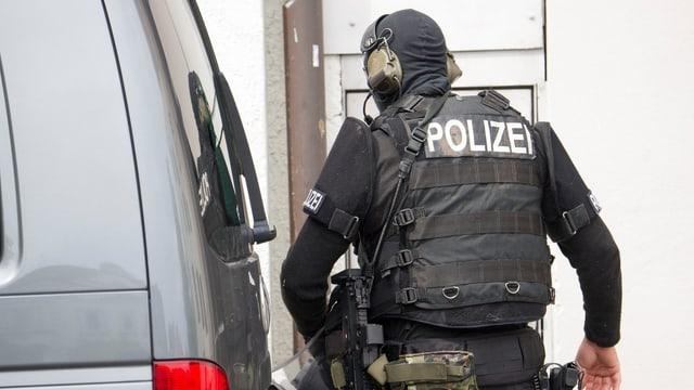 Polizist in Sicherheitsmontur von hinten fotografiert (Symbolbild)