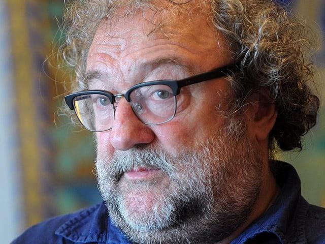 Ein Mann mit Bart, grauen Locken und schwarzer Brille.