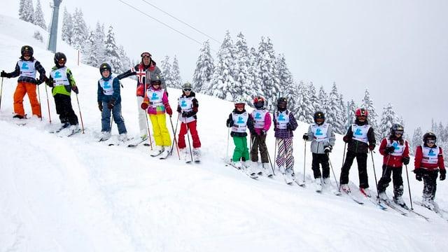 Skischüler in Reih und Gleid an einem Abhang