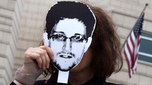 Eine Frau hält ein Snowden-Bild vor ihr Gesicht
