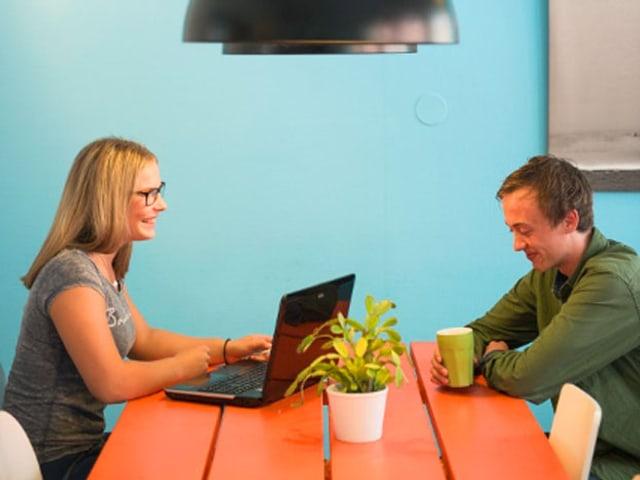 Eine Frau und ein Mann sitzen an einem orangen Tisch. Sie bedient einen Laptop.