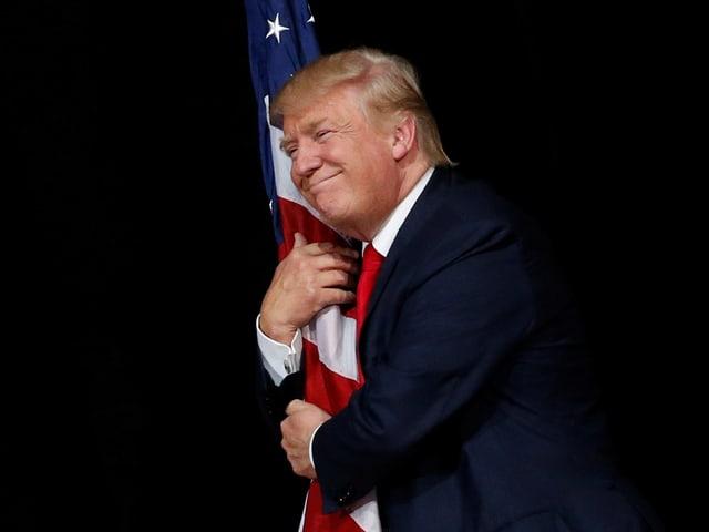 Trump umarmt eine US-Flagge.