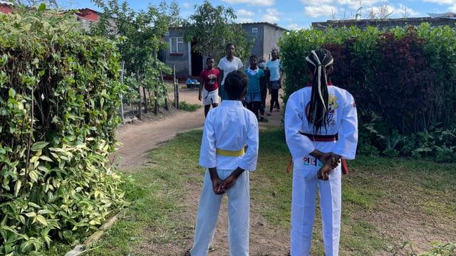 Zwei Taekwondo-Schüler von hinten auf Rasen