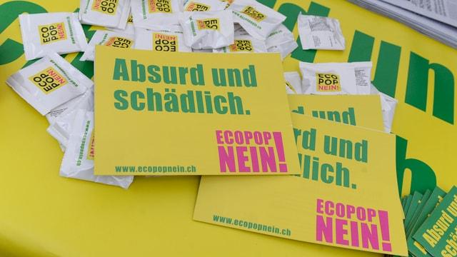 Placats mellens cun scrittira verda e rosa cunter l'iniziativa d'Ecopop cun il text Absurd und schädlich.