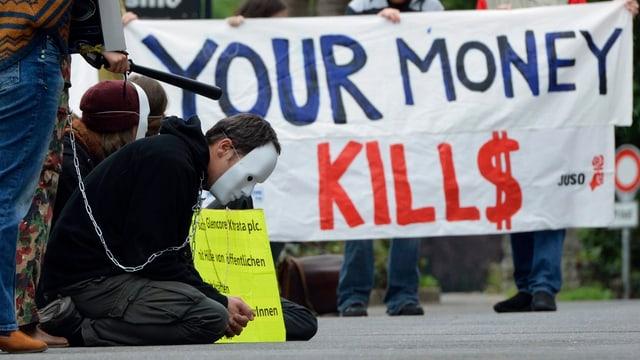 Ein Mann mit Maske kauert vor einem Plakat mit Aufschrift «your money kills»