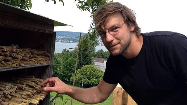 Claudio Sedivy steht vor einem Wildbienenhaus.