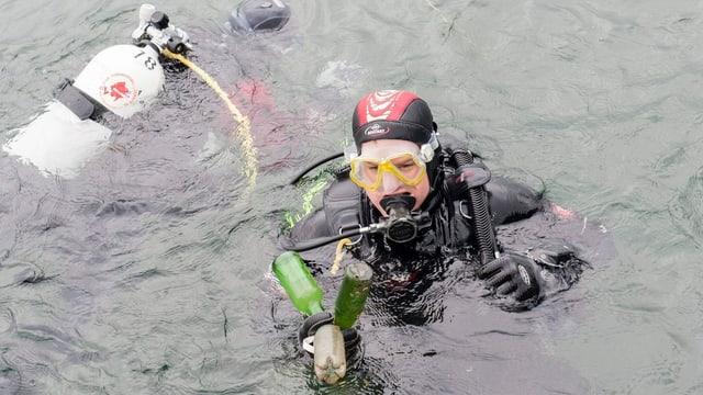 Zwei Taucher sammeln Abfälle im See ein. Einer der beiden Taucher ist unter Wasser, der andere hält Flaschen in der Hand.