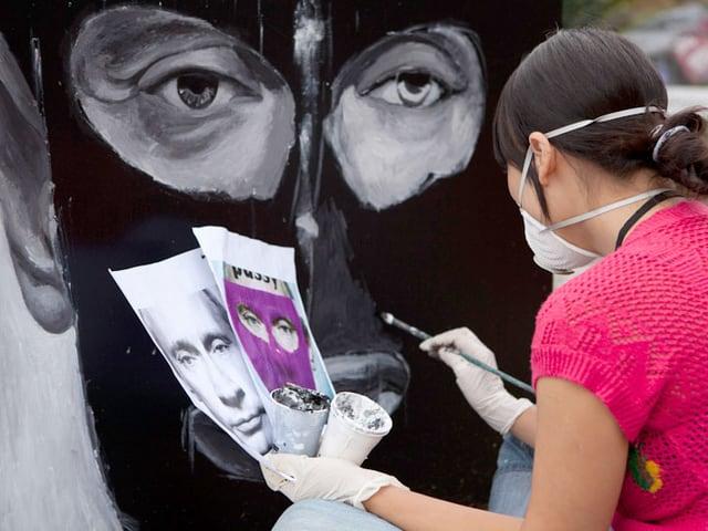 Eine Frau übermalt das Porträt von Putin mit schwarzer Farbe.