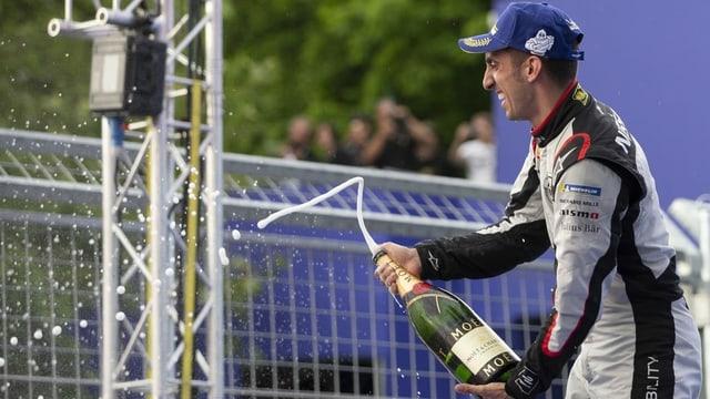 Sebastien Buemi jubelt mit einer Champagner-Flasche.