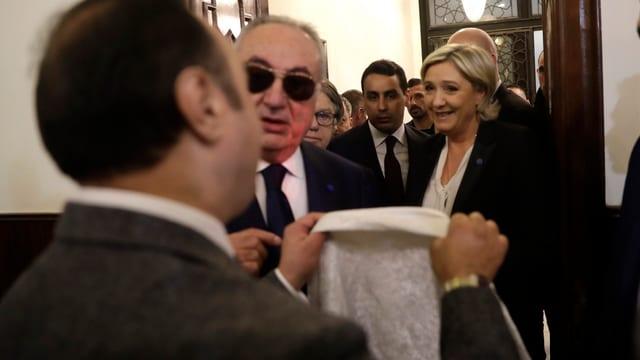 Le Pen in Beirut, vor ihr hält ein Mann ein Kopftuch in die Höhe.