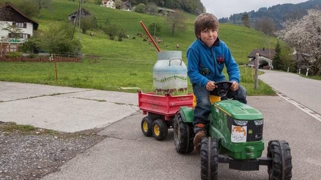 Ein Kind fährt mit einem Spielzeugtraktor. Auf einem Anhänger steht eine Milchkanne.