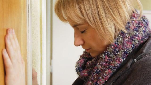 Eine blonde Frau stützt sich mit geschlossenen Augen an der Wand ab.