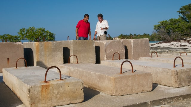 Fernando Martireno und ein Kollege betrachten mehrere Zement-Blöcke an der Küste.