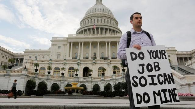 Ein Mann steht vor dem Kapitol. Er hält eine Pappschild vor sich hin. Darauf steht: Macht euren Job, dann kann ich meinen machen.