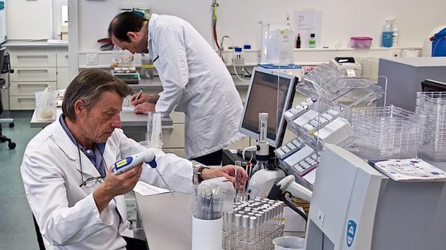 Zwei Männer in weissen Kitteln in einem Labor.
