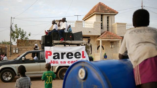 Schwarze Musiker fahren auf einem Auto auf einer staubigen Strasse durch ein Dorf.