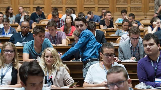 Viele Kinder und Jugendliche im Nationalratssal. Sie sitzen auf den Stühlen der Nationalräte.