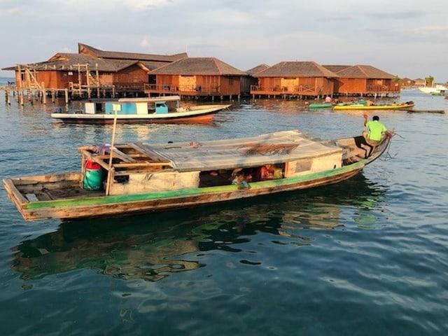 Ein Boot, im Hintergrund Wohnhäuser auf Pfählen im Wasser.