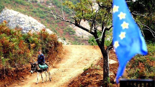 Europäiische Flagge im Vordergrund, im Hintergrund einen Mann auf einem Esel.