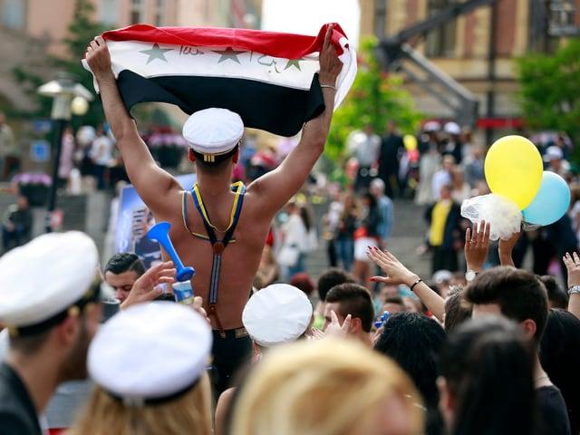 ein junger mann mit nacktem oberkörper hält an einem umzug für einen schulabschluss eine syrische flagge in die luft