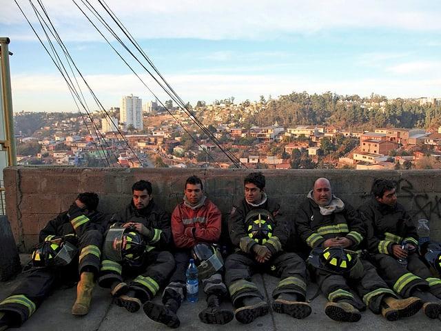 Erschöpfte Feuerwehrmänner sitzen am Boden