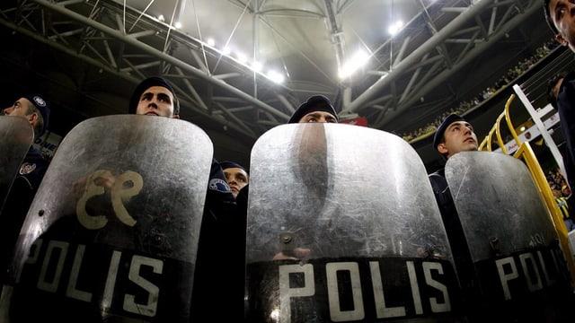 Polizisten hinter Plastik-Schilden in einem Fussballstadion.