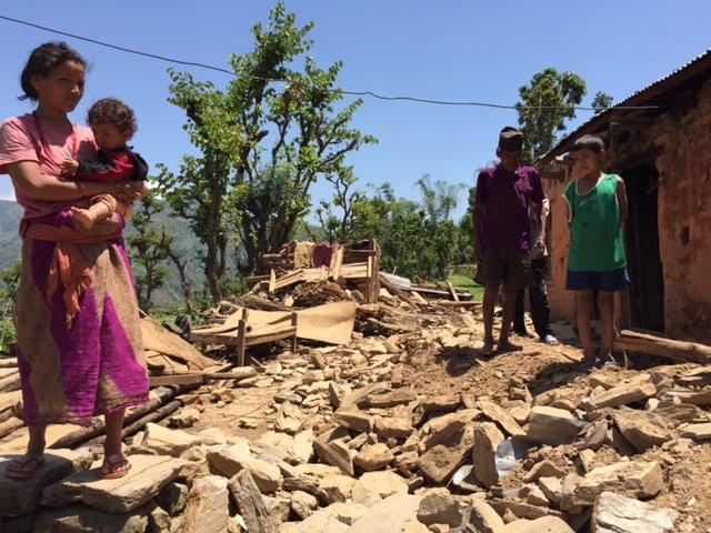 Eine Frau mit Kleinkind im Arm steht vor den Trümmern eines Hauses, daneben zwei Jungen.