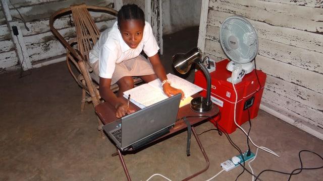 Schulmädchen arbeitet an Computer, betriebne von einem roten Power-Blox-Würfel