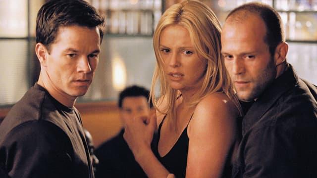 Eine blonde Frau zwischen zwei Männern.