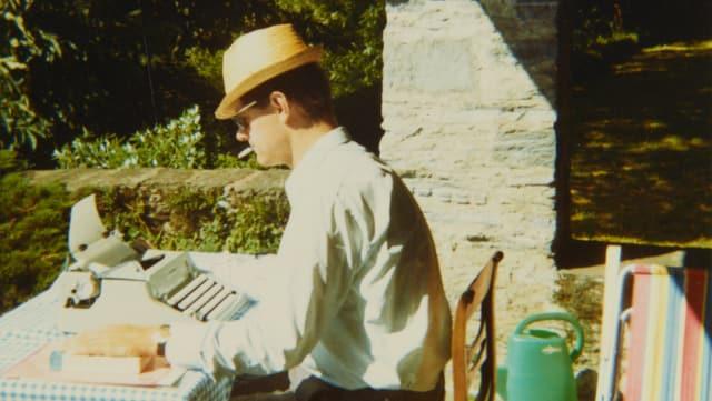 Mann mit Strohhut und Zigarette im Mund vor einer Schreibmaschine auf der Sonnenterasse eines Hauses