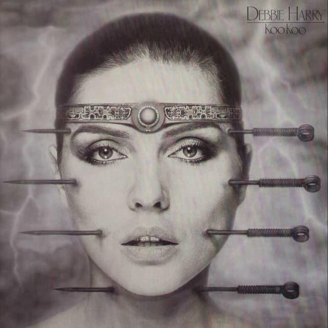 Zu sehen ist die Sängerin Debbie Harry. Vier grosse Nadeln durchboren ihr Gesicht. Abgesehen von den Nadeln sieht sie makellos aus.