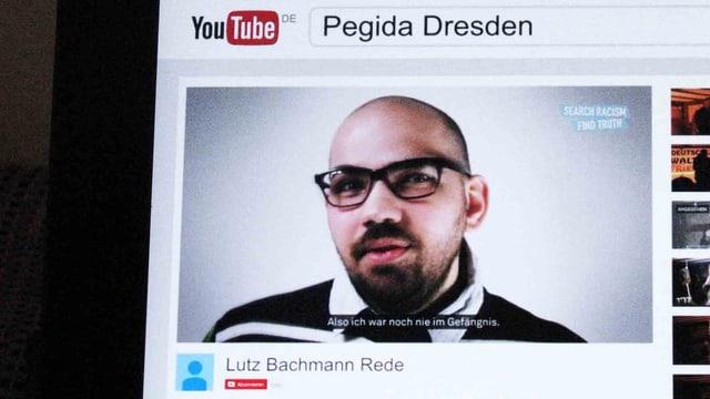 Mann mit Brille in einem YouTube-Fenster auf einem Bildschirm.