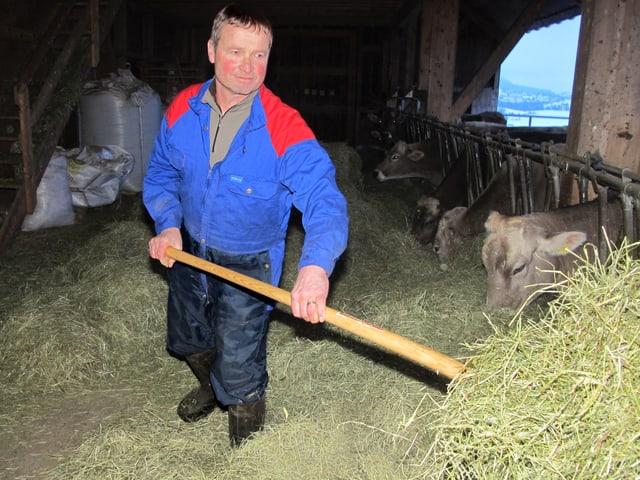 Mann füttert Tiere im Stall mit Heu.