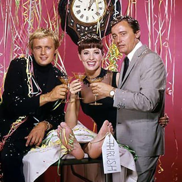 Zwei Männer und eine Frau prosten mit einem Glass in der Hand.